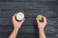 Kiwi and coconut in hands Royalty Free Stock Photo
