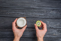Kiwi and coconut in hands Royalty Free Stock Photos