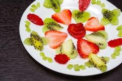 Kiwi cortado y fresas que mienten en modelo cuidadosamente desde arriba puesto en la placa blanca, como senn imagen de archivo libre de regalías