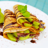 Kiwi crepes with chocolate sauce Stock Photos