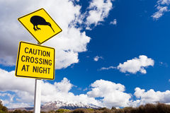 Kiwi Crossing road sign and volcano Ruapehu NZ. New Zealand Road Sign Attention Kiwi Crossing at road near active volcano of Mount Ruapehu in Tongariro National stock photography
