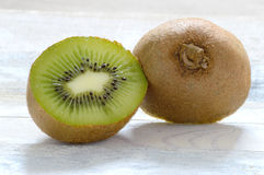 A kiwi cut in a half on a white wooden table Stock Photo