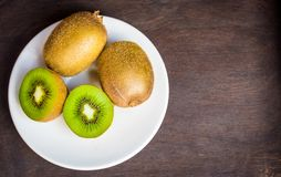 Kiwi d'un plat blanc avec le fond en bois foncé photographie stock