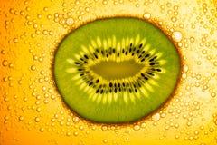 Kiwi dans l'eau jaune avec des bulles Image libre de droits