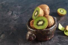 Kiwi on dark wood background. Fresh ripe kiwi fruits on vintage bowl on dark background royalty free stock photos