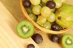 Kiwi de Cutted sur le conseil et le panier de fruits Photographie stock