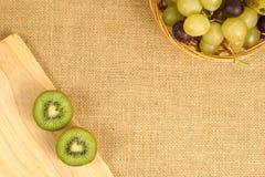 Kiwi de Cutted sur le panier en bois de conseil et de fruits Images stock
