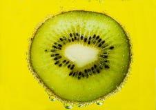 Kiwi de tranche dans les bulles Photographie stock