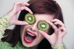 Kiwi divertente della holding della donna della frutta Fotografie Stock