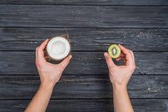 Kiwi e noce di cocco in mani Fotografia Stock Libera da Diritti