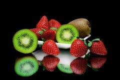 Kiwi en aardbeien op een plaat op een zwarte achtergrond met mirr Royalty-vrije Stock Fotografie