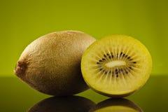 Kiwi en de helft op groen Stock Afbeeldingen