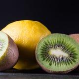 Kiwi et citron sur la table en bois noire, fond sombre, pièce pour Image libre de droits