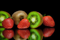 Kiwi et fraise mûrs sur un fond noir avec le refle de miroir Images stock