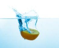 Kiwi falling into blue water with splash Stock Image