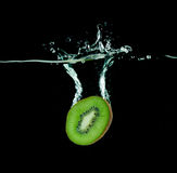 Kiwi Falling Into Water On Black Royalty Free Stock Images