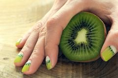 Kiwi art manicure. Kiwi and female hand with green and white moon nail art manicure royalty free stock photo