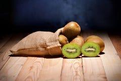 Kiwi friut in sack on floor wood. And black background stock photo