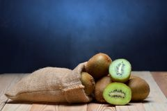 Kiwi friut in sack on floor wood. And black background stock image