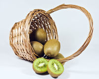 Kiwis. A wicker basket full of ripe kiwi fruit and one cut in half stock photo