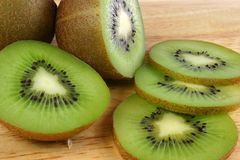 Kiwi Fruit. Sliced and halved kiwi fruit on wooden board Stock Photo