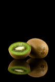 Kiwi fruit. On black with reflection Stock Photography