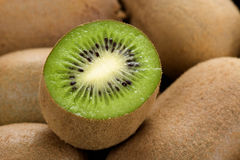 Kiwi fruit. Fresh kiwi fruit cutted in half with more fruits as background Royalty Free Stock Image
