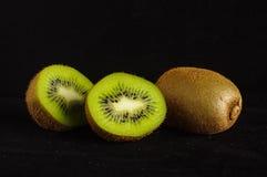 Kiwi fruit  on the black background Stock Photos