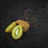 Kiwi Fruit close up. Kiwi fruit over a dark wooden table, shabby rustic mood Royalty Free Stock Image