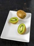 Kiwi Fruit close up. Kiwi fruit over a dark wooden table, shabby rustic mood Stock Images