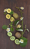 Kiwi fruit composition. Golden and green New Zealand kiwi fruit with flowers and leaves on dark wooden table royalty free stock images