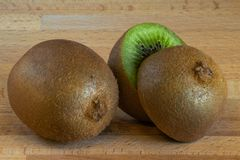 Kiwi fruit cut in half beside of another kiwi fruit royalty free stock photography