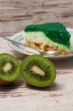 Kiwi fruit cut in half in front of green slice of cake royalty free stock photography