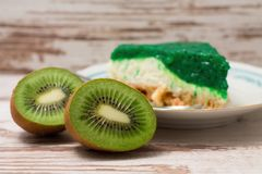 Kiwi fruit cut in half on white board in front of green cake stock photography