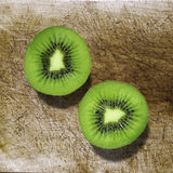 Kiwi fruit cut in half on a wooden board Royalty Free Stock Photo