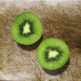 Kiwi fruit cut in half on a wooden board Royalty Free Stock Photo