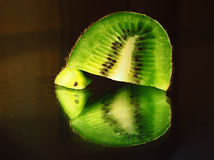 Kiwi fruit in a cut macro piece at mirror. The Kiwi fruit in a cut macro piece at mirror Royalty Free Stock Image