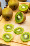 Kiwi fruit cut in slices on wooden cutting board. Close up Royalty Free Stock Photo