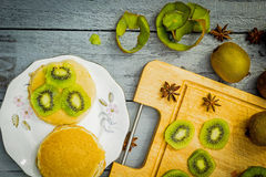 Kiwi fruit cut in slices on wooden cutting board. Kiwi fruit cut in slices, straberries and pancakes on wooden cutting board Royalty Free Stock Images