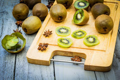 Kiwi fruit cut in slices on wooden cutting board. Kiwi fruit cut in slices, straberries and pancakes on wooden cutting board Stock Photo