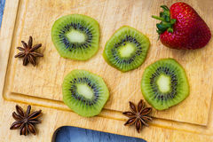 Kiwi fruit cut in slices on wooden cutting board. Upper view Stock Photos