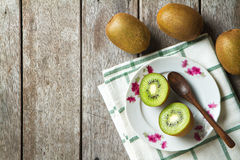 KIwi fruit on dish and spoon on wooden background. Royalty Free Stock Image