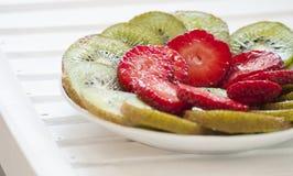Kiwi Fruit e fragole su bianco Immagine Stock