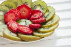 Kiwi Fruit e fragole su bianco Fotografia Stock