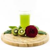 Kiwi - fruit en sap op houten raad met roze bloem Royalty-vrije Stock Foto's