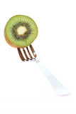 Kiwi fruit and fork. Slice of kiwi fruit held by fork isolated on white background royalty free stock photo