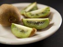 Kiwi Fruit. Fresh sliced kiwi displayed on off white plate Royalty Free Stock Photography