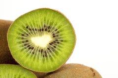 Kiwi Fruit. A halved kiwi fruit resting on whole fruits with white background stock image