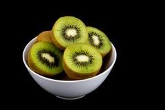 Kiwi Fruit i den vita bunken på svart bakgrund Royaltyfria Foton