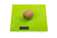 Kiwi fruit on kitchen scales Royalty Free Stock Photography